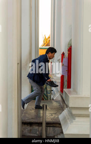 Man stepping into the main hall of Wat Pho in Bangkok, Thailand. - Stock Photo