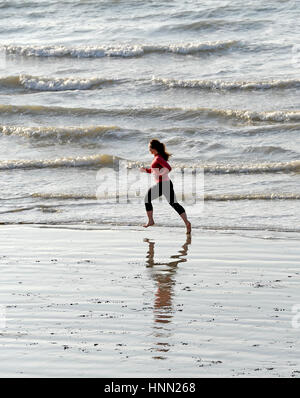Brighton Sussex, UK. 15th Feb, 2017. A young woman enjoys an early morning run on the sand at low tide along Brighton - Stock Photo