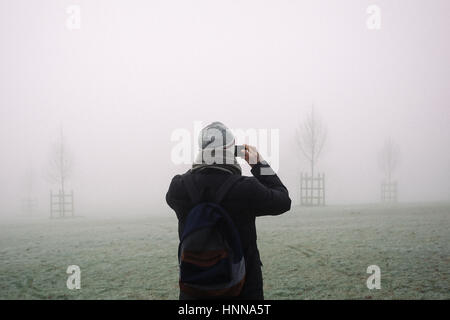 Young man in winter coat, hat and scarf taking photos with his mobile phone of London park, disappearing in the - Stock Photo