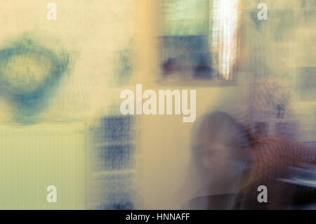 Blurred abstract view of young woman bending in a room alone - Stock Photo