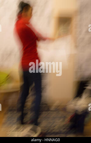 Blurred abstract view of a woman with red clothes standing in a room with papers in her hand - Stock Photo