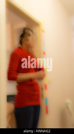 Blurred abstract view of a woman with red clothes standing in a room touching her chin - Stock Photo