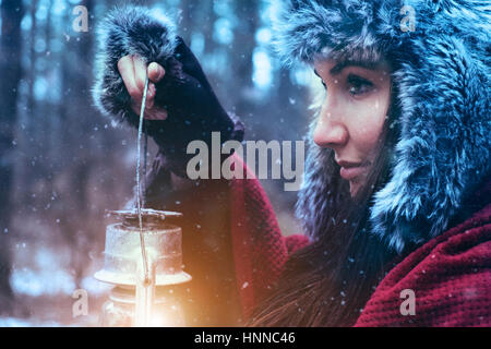 Woman with oil lamp in winter forest - Stock Photo