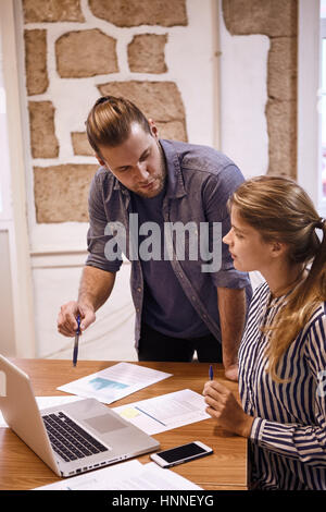 Professional business man with a pen in his hand discussing something with the businesslady while looking at the - Stock Photo