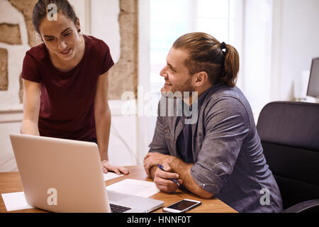 Two young professionals in a discussion with the business woman showing him something on the laptop screen while - Stock Photo