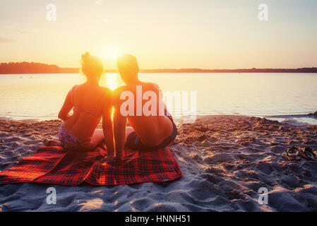 Romantic couple on the beach at colorful sunset - Stock Photo