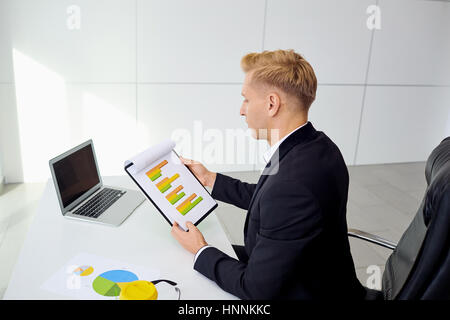 Businessman working at his desk with a laptop in the office - Stock Photo