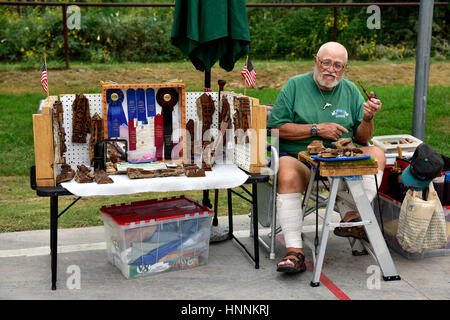 Man displaying and selling his wood carvings in local farmers market, Cornville, Arizona - Stock Photo
