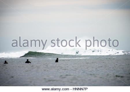 People swimming in sea against sky - Stock Photo