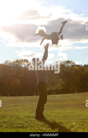 Side view of father playing with daughter while standing on grassy field - Stock Photo