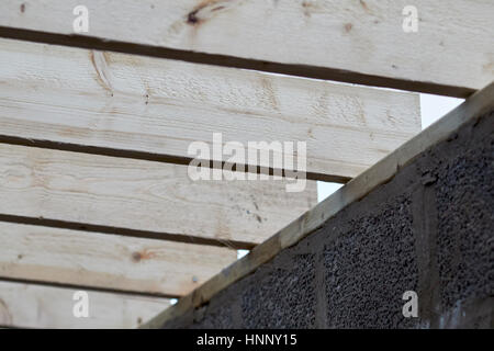 row of wooden roof rafter timbers ending on wall plate in extension construction in the uk - Stock Photo