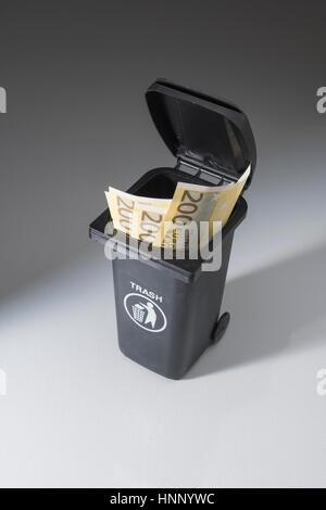 200 Euro banknotes / bills in a toy wheely bin / wheeliebin / trash bin. Metaphor for wasting money. - Stock Photo