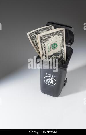 US $1 Dollar banknotes / bills in a toy wheely bin / wheeliebin / trash bin. Metaphor for wasting money. - Stock Photo