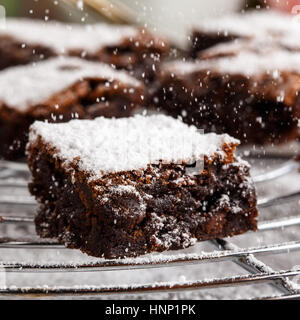 homemade chocolate brownies with icing sugar on a cake rack. - Stock Photo