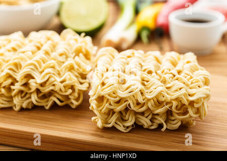 Asian instant noodles on a wooden board. - Stock Photo