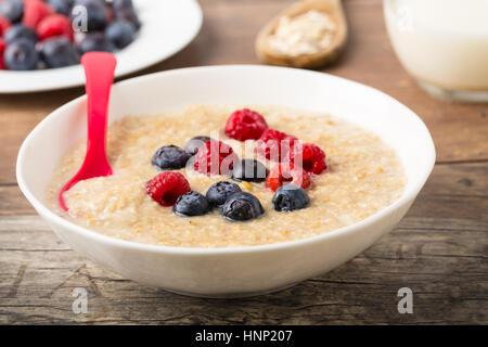 homemade sweet porridge mit blueberries and raspberries - Stock Photo