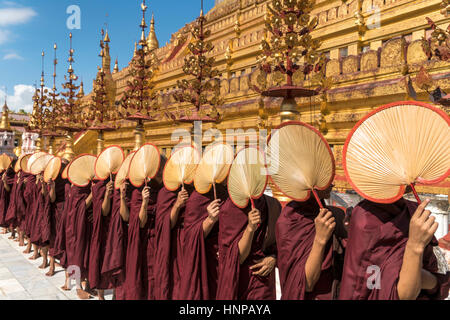 Monks with fans waiting for donations, Shwezigon Pagoda, Bagan, Myanmar - Stock Photo