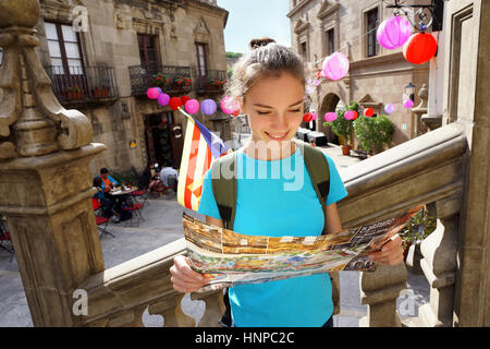 Travel in Spain. Tourist holding travel map. Young girl looking at map with famous landmarks. - Stock Photo