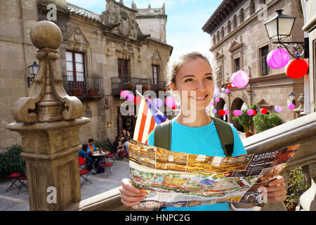Travel in Spain. Tourist holding travel map. Smiling girl walking along spanish streets in Valencia - Stock Photo