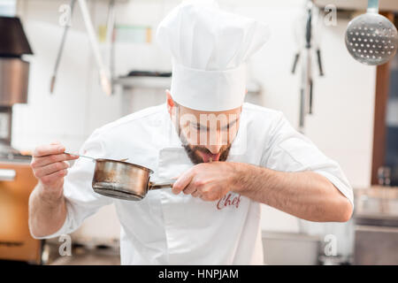 Handsome chef cook in uniform tasting sause at the kitchen - Stock Photo