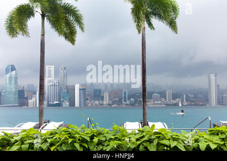 Girl swims in Infinity Pool on the roof of Marina Bay Sands Hotel on July 9, 2013 in Singapore. - Stock Photo