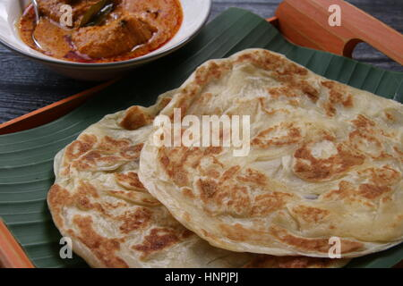 Roti Prata. Indian-influenced flatbread. Plated on a banana-leaf-lined bamboo tray with the chicken curry served - Stock Photo
