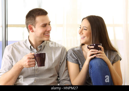 Front view of a happy couple talking and drinking coffee sitting on the floor near a window at home - Stock Photo