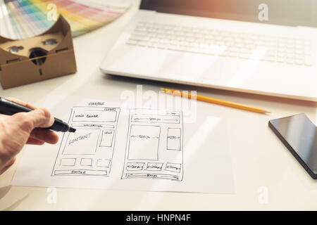 designer drawing website development wireframe on paper in office - Stock Photo