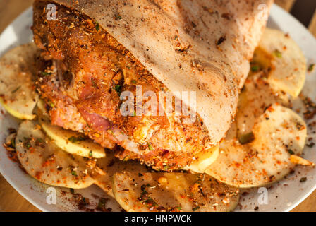 Marinated pork knuckle with sliced quince, spices and herbs closeup - Stock Photo
