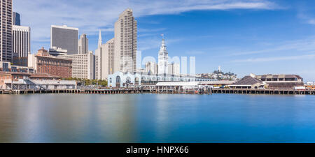 Panoramic view of San Francisco skyline with historic Ferry Building at famous Embarcadero street on a sunny day - Stock Photo