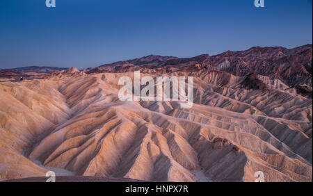Scenic panoramic view of amazing sandstone formations at famous Zabriskie Point viewpoint in beautiful post sunset - Stock Photo