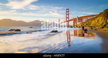Classic panoramic view of famous Golden Gate Bridge seen from scenic Baker Beach in beautiful golden evening light at sunset, San Francisco, California