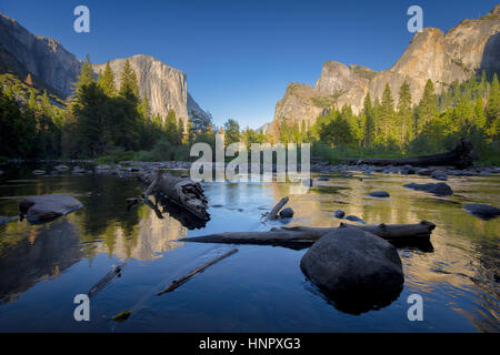 Classic view of scenic Yosemite Valley with famous El Capitan rock climbing summit and idyllic Merced river in beautiful evening light at sunset, USA Stock Photo