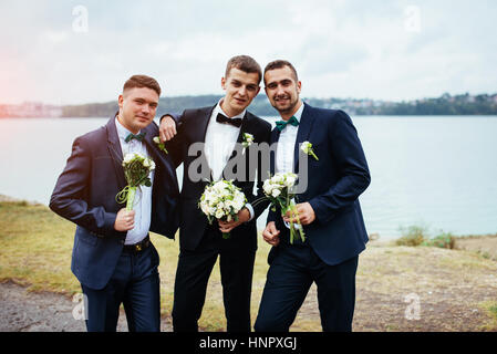 Confident smiling handsome groom in black suit with two groomsma - Stock Photo