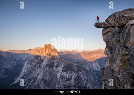 A male hiker standing on an overhanging rock at Glacier Point enjoying the breathtaking view towards famous Half - Stock Photo