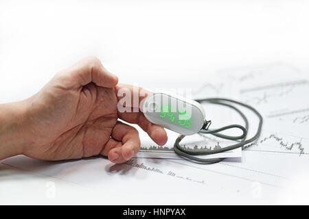 Blood oxygen meter on mans finger. - Stock Photo