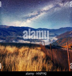 Fantastic starry sky and majestic mountains in the mist. Dramati - Stock Photo