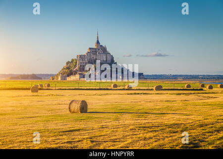 Beautiful view of famous historic Le Mont Saint-Michel in golden evening light at sunset in summer with hay bales on fields, Normandy, northern France