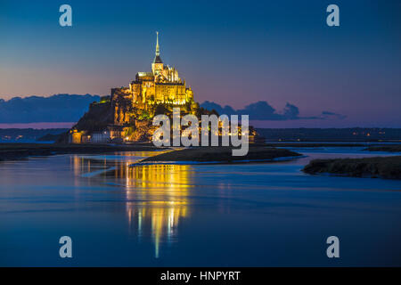 Classic view of famous Le Mont Saint-Michel tidal island in beautiful twilight during blue hour at dusk, Normandy, - Stock Photo