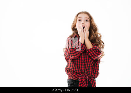 Surprised curly little girl in plaid shirt covered opened mouth by hands over white background - Stock Photo