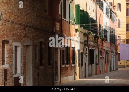 Narrow cobblestone alley in the historical center of Venice, Veneto, Italy, Europe - Stock Photo
