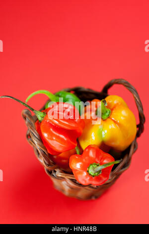 Small basket filled with mini hot peppers - Stock Photo