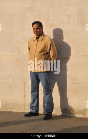 Man standing against a wall having hiis picture taken. - Stock Photo