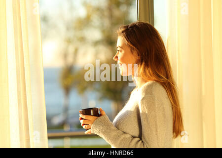 Side view portrait of a single relaxed girl looking the sea outside through a window and holding a coffee mug at - Stock Photo