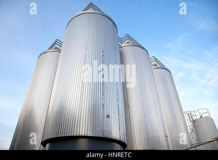 Outdoor brewery tanks against blue sky. - Stock Photo