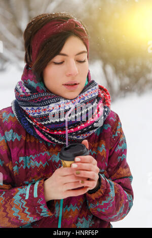 Young woman in winter forest with cup of hot coffee - Stock Photo
