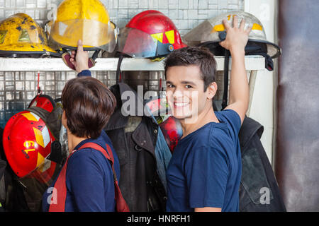Happy Firefighter With Colleague Removing Helmet - Stock Photo