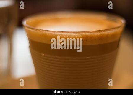 Coffee in glass mug. Flat white. Narrow depth of field. - Stock Photo