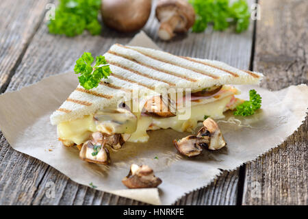 Pressed and toasted double panini with ham, cheese and mushrooms served on sandwich paper on a wooden table - Stock Photo