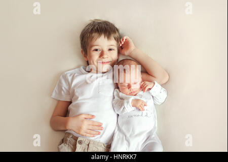 Little brother hugging her newborn baby. Toddler kid meeting new sibling. Cute boy and new born baby girl relax - Stock Photo